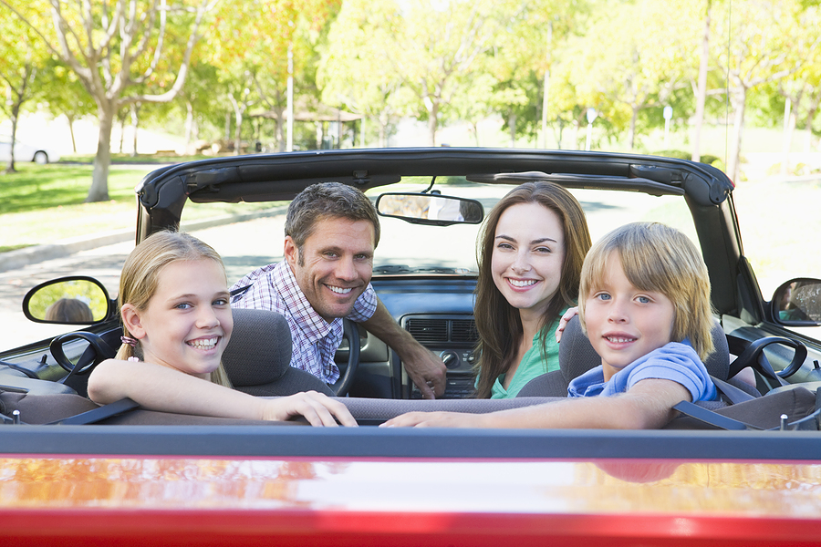 Smiling family in convertible red car