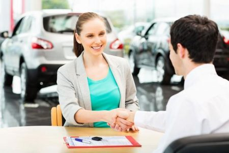Smiling woman shaking hands with dealer. TNL Car Title Loans