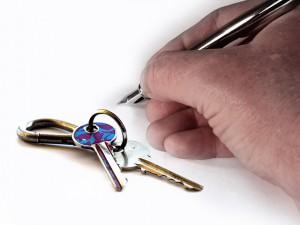 man's hand holding a pen, keys