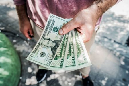 Man holding 20 dollar bills in hand. The Net Lender can help you get a loan!